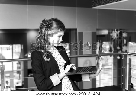 Young beautiful women standing in a cafe and working on laptop. monochrome