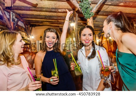 Young beautiful women with cocktails in bar or club - stock photo