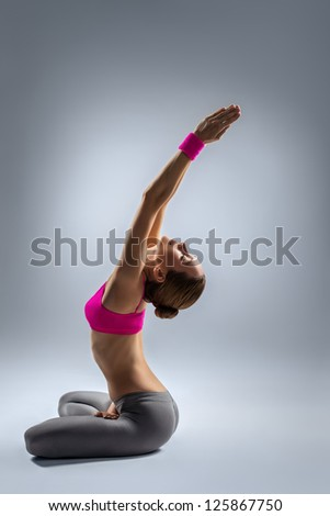 young beautiful yoga posing on a gray studio background - stock photo