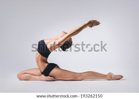 young beautiful yoga posing on a gray studio background - stock photo