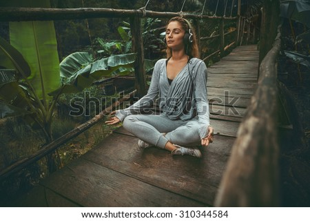 Young beautiful yoga woman listen to the music on suspension bridge in the tropic forest