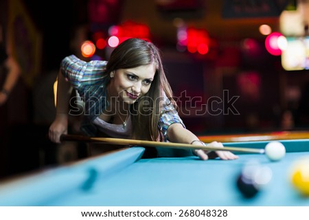 Young beautiful young lady aiming to take the snooker shot while leaning over the table in a club - stock photo