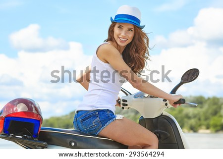 Young beautifulsexy woman sitting on a scooter outdoor