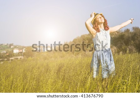 Young,beauty and caucasian woman feeling good and smiling at the sky,alone in a countryside - lifestyle, outdoor and people concept - stock photo