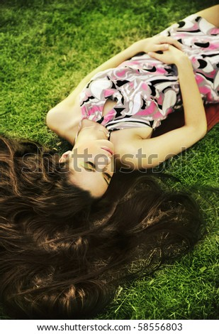 Young beauty brunette laying on the grass - stock photo