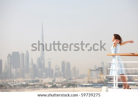 young beauty brunette woman standing on cruise liner deck, putting hands apart, city on background - stock photo