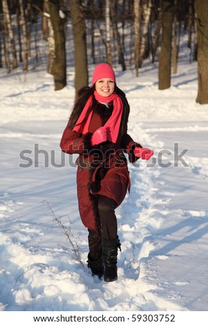 young beauty girl in pink scarf and hat smiling and walking to front outdoor at winter day - stock photo