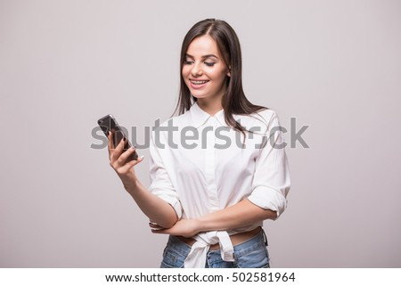 Young beauty girl look at phone on grey background