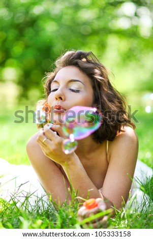 Young beauty girl lying on summer green grass and blowing colorful soap bubbles