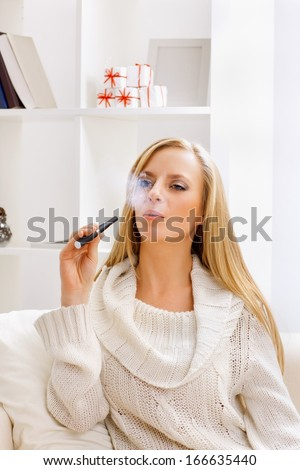 young beauty girl with e-cigarette  in light room  - stock photo