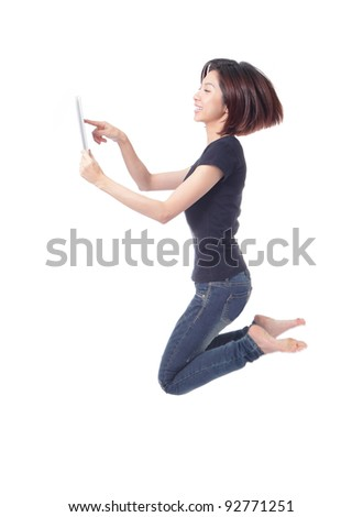 Young beauty happy jump and using tablet pc in the air isolated on white background, model is a cute asian - stock photo