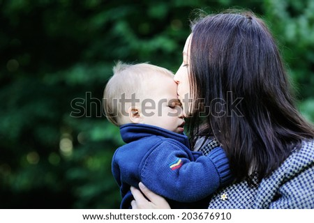 Young beauty mother hugs  and kisses her cute baby son outdoors in the park - stock photo