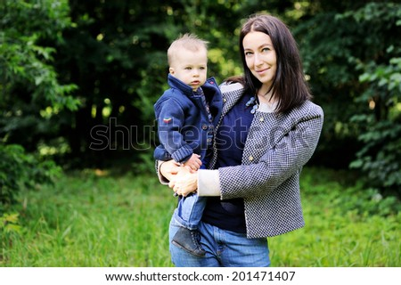 Young beauty  mother hugs her cute baby son outdoors in the park