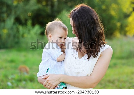 Young beauty mother hugs her cute baby son outdoors in the park  - stock photo
