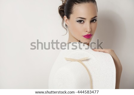 young beauty portrait with pink lips holding summer white hat, studio