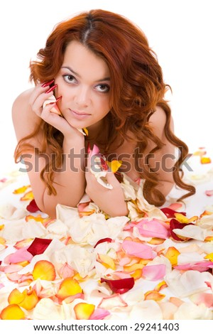 young beauty sensual woman with long hair lying on petals - stock photo