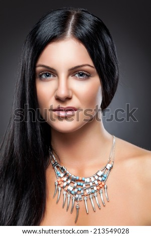 Young beauty with long dark hair wearing a necklace - stock photo