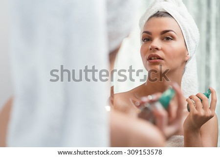 Young beauty woman applying perfume after bath - stock photo