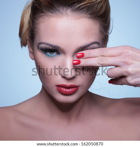 young beauty woman covering one eye with her fingers with red manicure