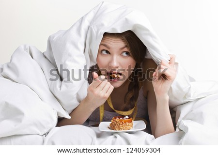 young beauty woman eating dessert under cover on white background - stock photo