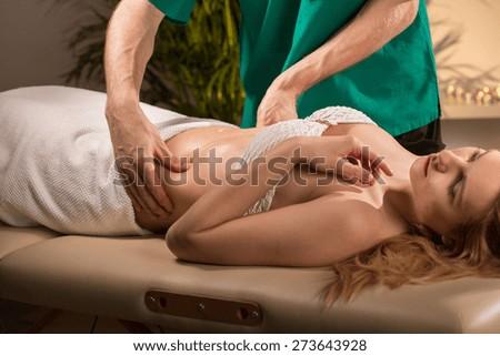 Young beauty woman having done abdominal massage - stock photo
