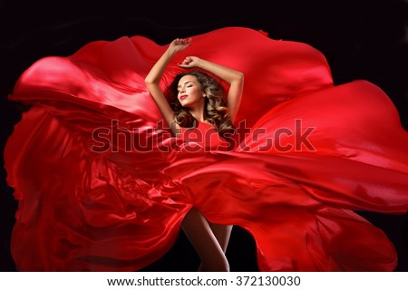 Young beauty woman in red waving flying  dress. Dancer in silk dress. - stock photo