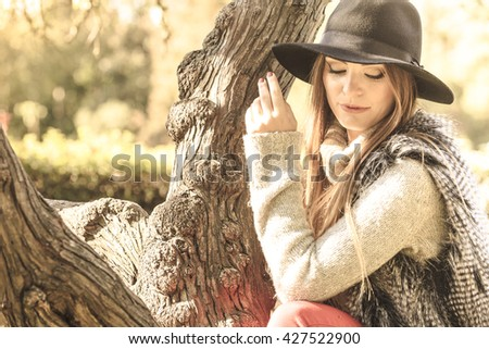 Young beauty woman wearing stylish autumnal clothes relaxing in park. Portrait of fashionable caucasian girl student resting on air. - stock photo