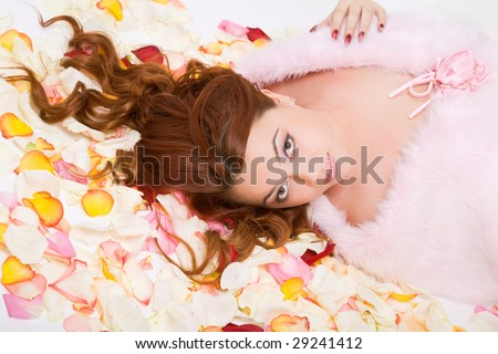young beauty woman with long hair lying on petals