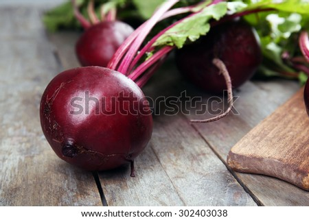Young beets with leaves on wooden table close up - stock photo