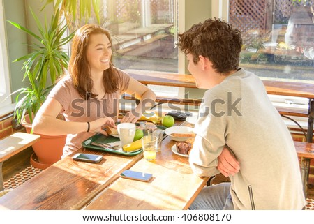 Young best friends making breakfast with morning light through the window in modern hostel. People couple sitting on the bench and speaking together a funny story. Main focus on the girl - stock photo