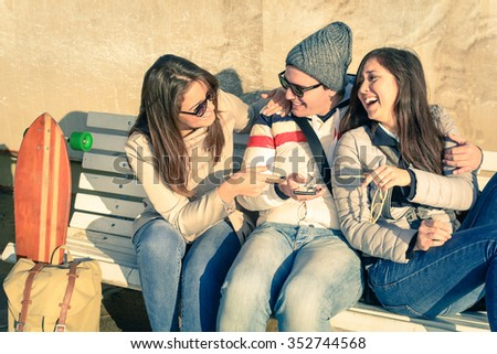 Young best friends playing with smartphone in urban alternative location. Group of cheerful friends concept of friendship and fun with new trends and technology. People connected to social media. - stock photo