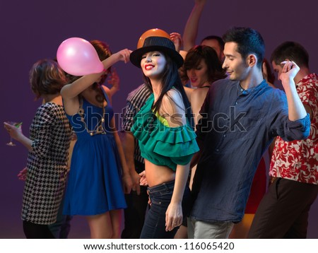 young beuatiful gilr smiling to the camera, dancing with young guy, with people dancing in the background - stock photo