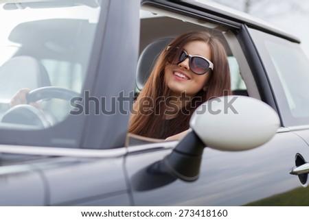 Young beuatiful woman driving a car. - stock photo