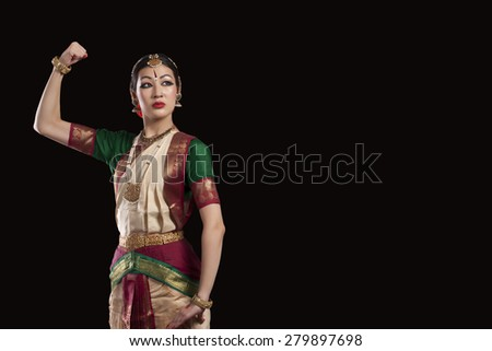 Young Bharatanatyam dancer flexing muscle over black background - stock photo