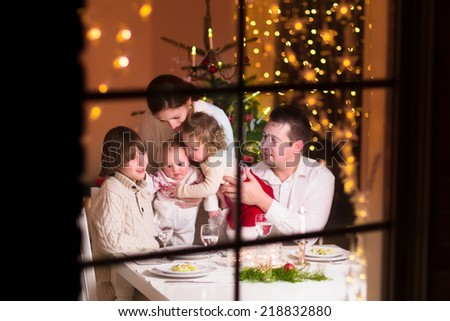 Young big family celebrating Christmas enjoying dinner, view from outside through a window into a decorated living room with tree and candle lights, happy parents eating with three kids