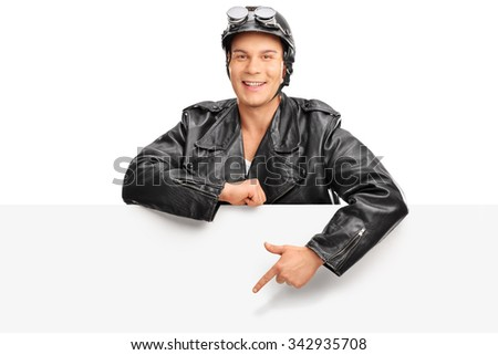 Young biker in a black leather jacket standing behind a blank billboard and pointing towards it with his finger isolated on white background - stock photo