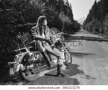 Young biker man with long hair and beard wearing a leather jacket gloves and boots sitting on his motorcycle on the open road. Sunny day in the mountains. Tilt shift soft effect. Black and white - stock photo