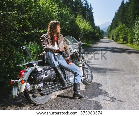 Young biker man with long hair and beard wearing a leather jacket gloves and leather boots sitting on his motorcycle on the open road. Sunny day in the mountains