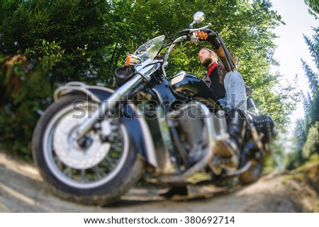 young biker with beard driving his cruiser motorcycle on road in the forest. Man is wearing leather jacket and blue jeans. Low point of view. Tilt shift lens blur effect - stock photo