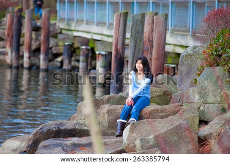 Young biracial teen girl in blue shirt and jeans sitting on large boulders along lake shore, looking out over water - stock photo