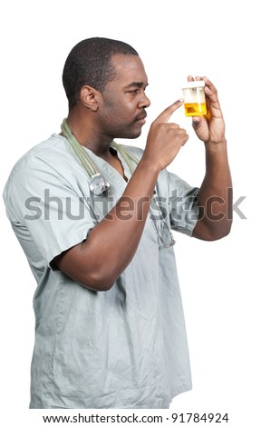 Young black African American man doctor in scrubs holding a urine sample - stock photo