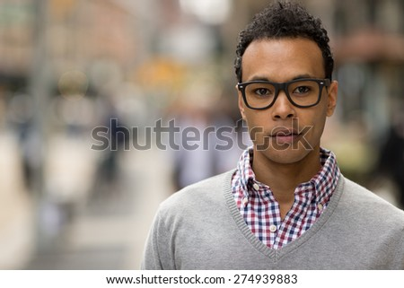 Young black African Asian man in city serious face portrait