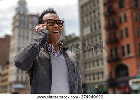 Young black African Asian man in city talking on cell phone