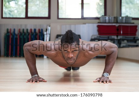 Young black african man portrait doing push up exercise at the gym.  - stock photo
