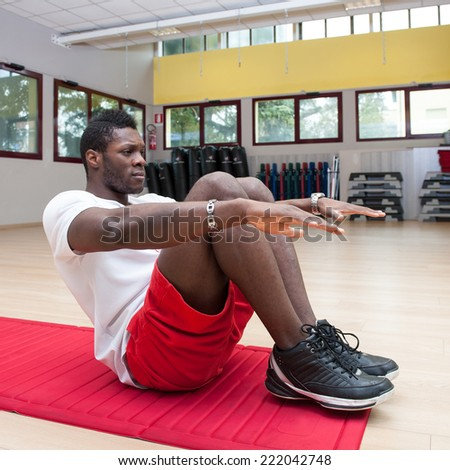 Young black african man portrait exercising abdominal muscles at the gym.  - stock photo