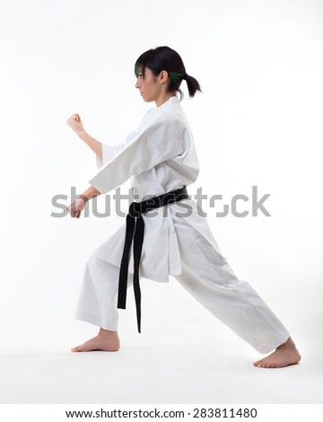 Young black belt fighter training Karate. Isolated woman portrait on white background