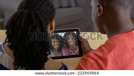 Young black couple talking to friends over tablet computer video chat - stock photo