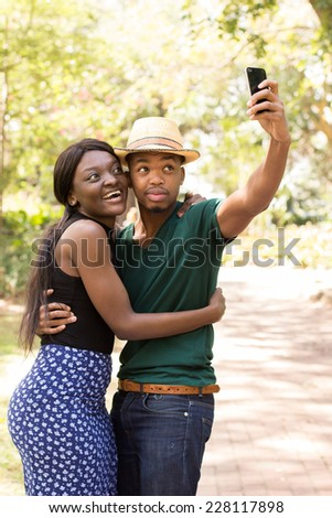 Young Black couple using cellphone and taking selfies - stock photo