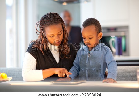 Young black family in fresh modern kitchen - stock photo