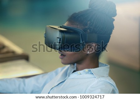 Young black female sitting and using VR headset